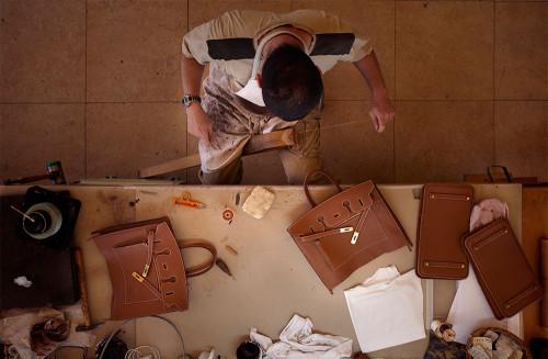 A craftsman piecing together a leather handbag   Source: Courtesy Hermès
